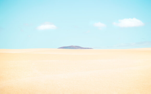 Desert landscape with a mountain between the dunes on sunny day.