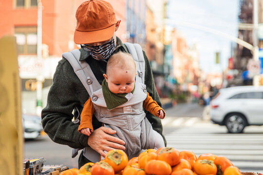 Father with baby girl buying persimmons on street in city during coronavirus outbreak