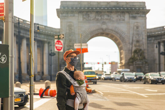 Man wearing face mask carrying daughter in baby carrier while standing on street in city during COVID-19