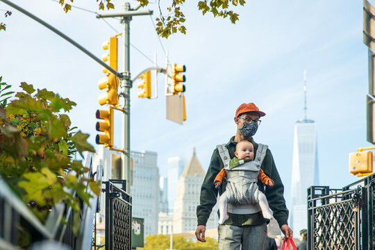 Father carrying cute daughter in baby carrier while walking in city during COVID-19