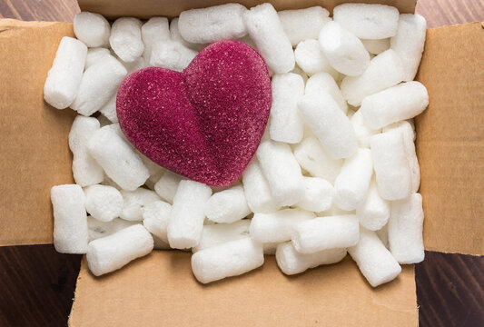 red heart in a cardboard box with styrofoam packing peanuts for concept of fragile heart