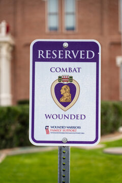 Florence, AZ - Nov. 27, 2019: Parking space reserved sign for Combat Wounded Veterans shows the Purple Heart Award and Wounded Warriors Family Support logo.
