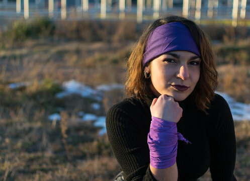 Caucasian young adult female with purple headscarf and wrist scarf.concept of feminism