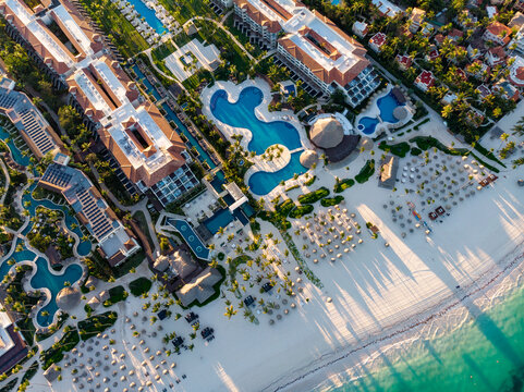 Aerial drone view of beach resort hotels with pools, umbrellas and blue water of Atlantic Ocean, Bavaro, Punta Cana, Dominican Republic