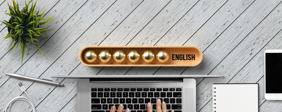 stylized loading bar with the word ENGLISH in English and office equipment on wooden background
