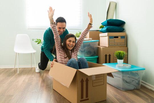 Latin man pushing his girlfriend sitting inside a box