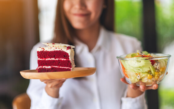 Closeup image of a young woman holding a plate of velvet cake and a bowl of vegetables salad