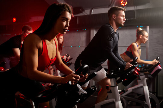 men and women biking in gym, exercising legs doing cardio workout cycling bikes, spinning in health club, wearing tracksuit sportive outfit