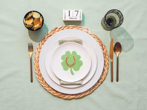 Beautiful festive table setting for St.Patrick's day with cutlery and lucky symbols. Top view of Saint Patrick's day holiday table with green linen tablecloth. Flat lay.