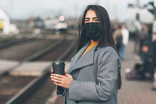 Happy girl in a mask stands waiting for the train at the station with coffee in her hands.
