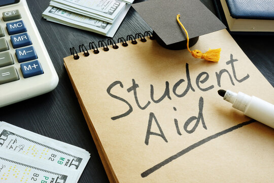 Student aid sign with small graduation cap and money.