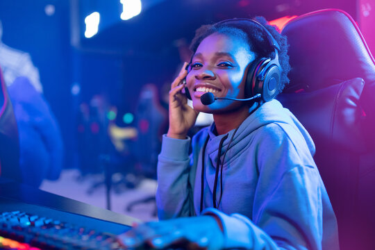 Young african happy woman professional gamer win in online video game with headphones, neon background