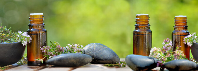 Fototapeta bottles of essential oil and lavender flowers  with pebbles on green background