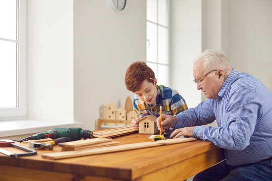 Experienced old carpenter teaching teen boy new handwork skills. Senior man and child working with wood together. Happy grandfather and little grandson making wooden toy houses at carpentry workshop