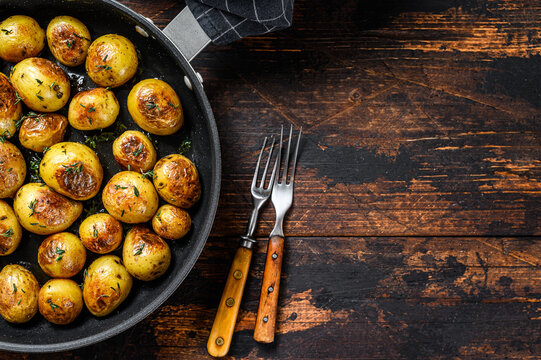 Baked baby potatoes in a cast iron skillet. Dark wooden background. Top view. Copy space