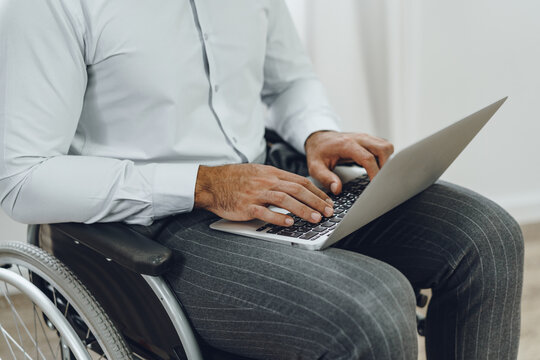 Disabled man in a wheelchair using laptop