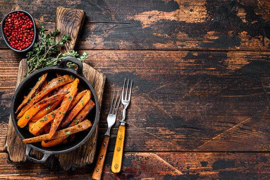 Vegetarian Oven baked sweet potato fries. Dark wooden background. Top view. Copy space
