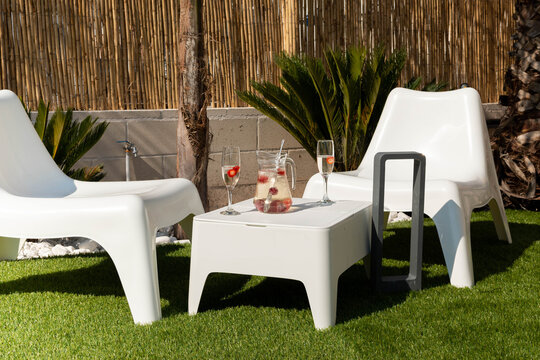 terrace with white chairs and table on grass