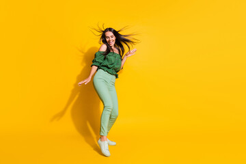 Photo portrait full body view of dancing girl isolated on vivid yellow colored background with blank space