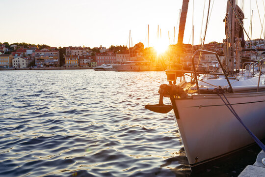 warm morning sunlight through the rigging of luxury yacht moored in harbour of Losinj town, Croatia.