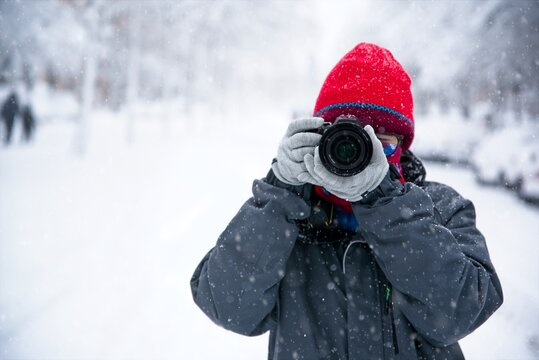 Teenage girl takes photos with her camera on the snow