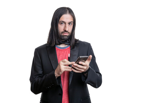 A man with long hair and a beard with an electronic cigarette with sticks and a phone in his hands on a white background. He is wearing a black jacket and a red T-shirt and a bow tie around his neck.