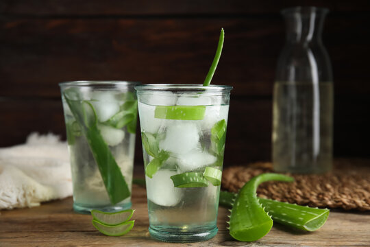 Fresh aloe drink with ice cubes on wooden table