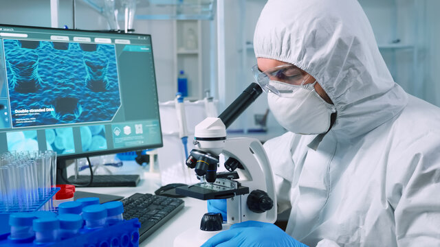 Medical research scientist in coverall conducting vaccine development under digital microscope in a biological applied science laboratory. Lab engineer in ppe suit working on medical treatment
