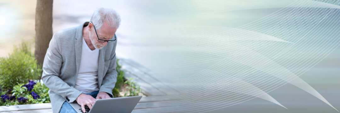 Mature businessman using laptop outdoors; panoramic banner