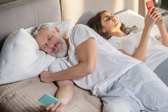 Woman and turned away man lying with smartphones