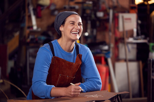 Female Blacksmith Wearing Headscarf Working On Design In Forge