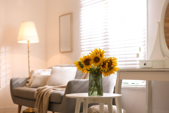 Beautiful bouquet of sunflowers in vase on white table indoors. Space for text