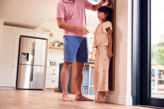 Asian Father Measuring Daughter On Wall Scale At Home As She Stands On Tip Toes