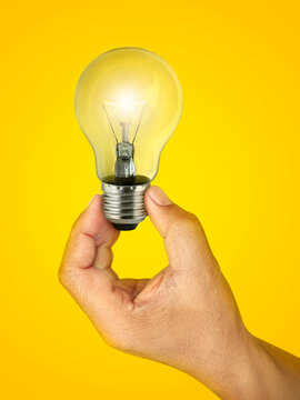 Concept creativity with Hand holding glowing light bulb  that shine glitter on yellow background