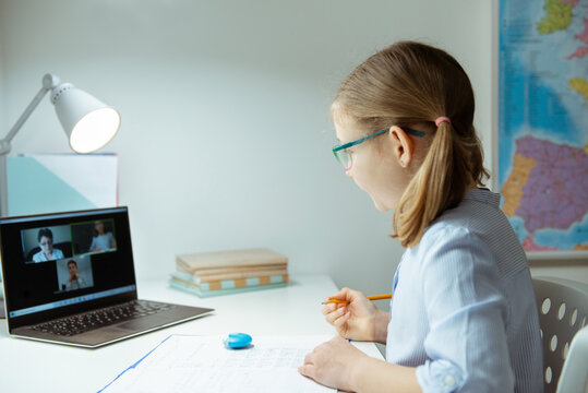 Little school girl having virtual lesson at home using laptop during homeschooling at pandemic quarantine
