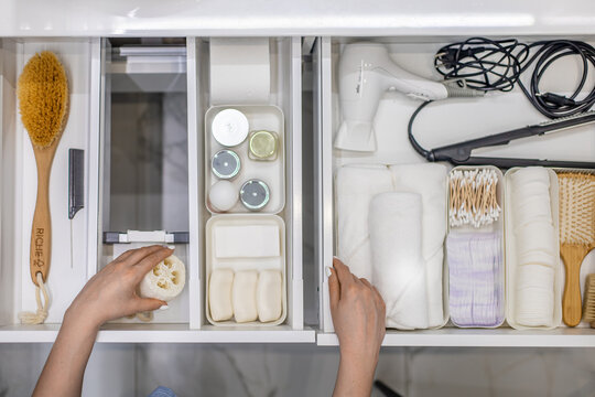 Top view of woman hands neatly organizing bathroom amenities and toiletries in drawer in bathroom.