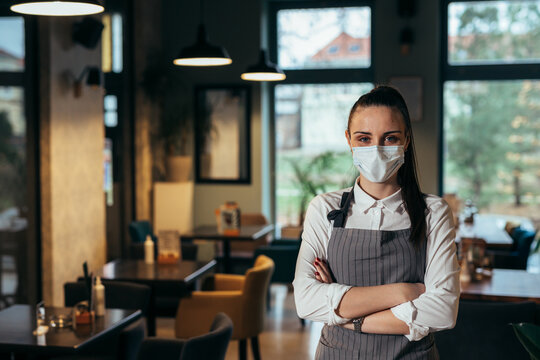 waitress standing arms crossed in restaurant, posing with protective face mask, covid-19 concept