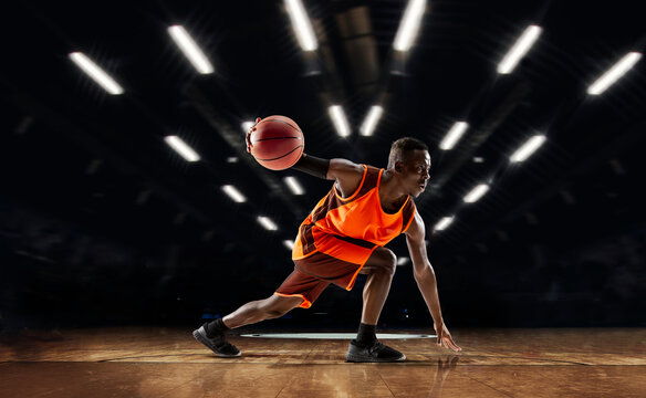 Team supporting. African-american young basketball player in action and motion in flashlights over dark gym background. Concept of sport, movement, energy and dynamic, healthy lifestyle. Arena's