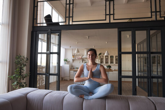 Woman do youga or pilates exercise at home. She is in sportswear and using mat. Slim flexible and fit brunette caucasian woman. She relax in meditation mood and smiles cheerfully. Space for text