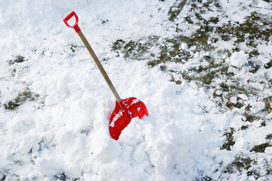 View of a red shovel in snow and red sledge in winter
