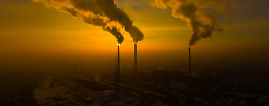 Power Plant emissions seen above the city  during sunrise. Environmental pollution. Factory pipe polluting air.Panorama sunset. Smoking pipes Aerial view,