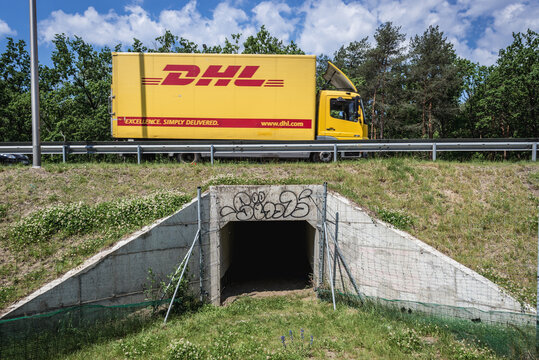 Warsaw, Poland - June 17, 2020: Yellow DHL truck over wildlife tunnel in Warsaw city
