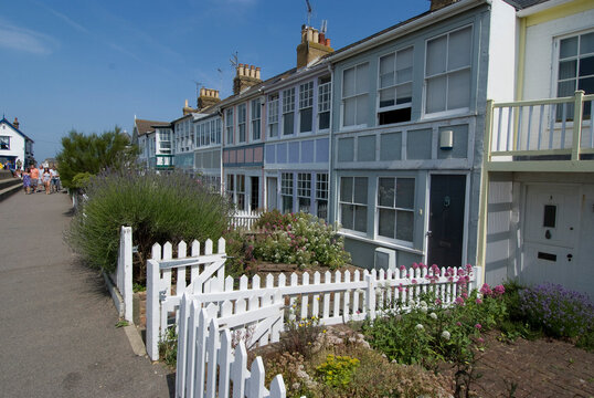 White picket fences in front of holiday waterside houses, Whitstable, Kent.