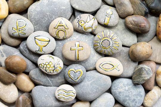 Christliche Symbole auf Steine gemalt.