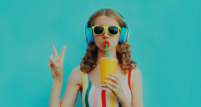 Portrait of modern young woman drinking a juice with headphones listening to music posing on a blue background