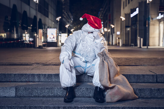 Photo of a desperate beggar, dressed in the coverall used against the coronavirus, the mask, and the beard and hat of Santa Claus, sitting in the stairs in an empty square.