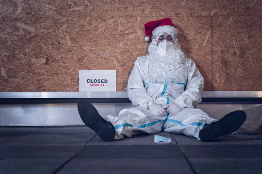 Photo of a man, dressed as Santa Claus, but with a coverall, mask and glasses, used to protect himself from the coronavirus, sitting on the floor, in front of his closed store.