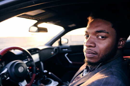 African American Business Man in Sports Car At Sunset
