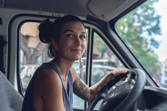 Young woman, with tattoos and piercings, driving a van, looks at the room with satisfied expression.