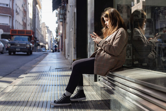 Teenage girl with a smartphone on a street in Buenos Aires